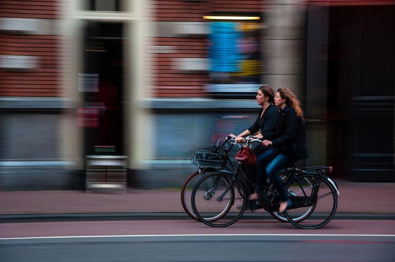zwei Fahrradfahrer in der Innenstadt von der Seite fotografiert
