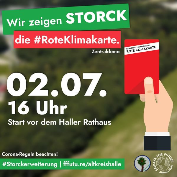 rote Karte in der Hand vor grünem unscharfem Hintergrund zur Demo am 02.07. um 16 Uhr