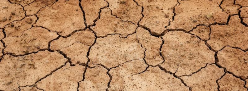 Ausgetrockneter, rissiger rötlicher Boden, der starken Wassermangel hat