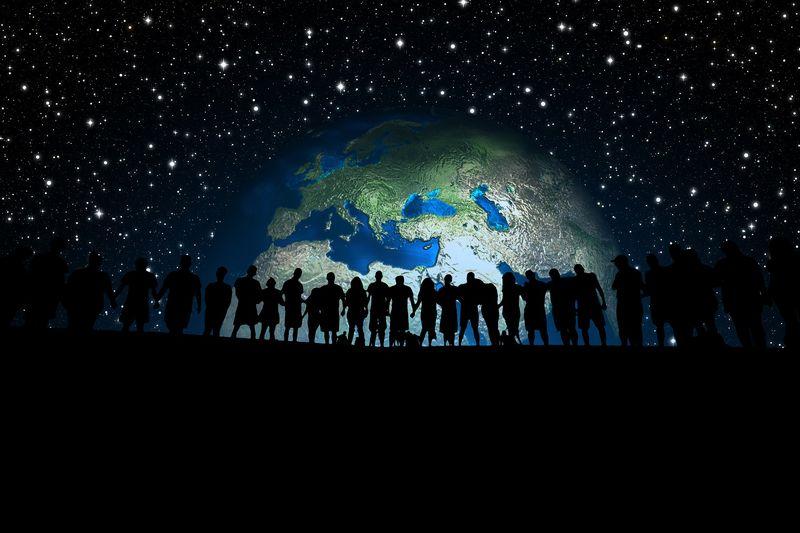 Leitende Erde vor schwarzem Hintergrund, Silhouetten in schwarz von einer Menschenkette davor