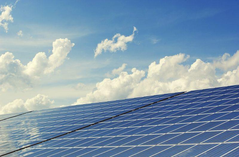 Photovoltaik Anlage von der Seite mit Sonne vor blauem Himmel im Hintergrund