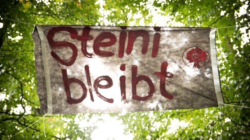 """Banner vor Blick auf grüne Baumkronen mit dem Text in Rot: """"Steine bleibt"""""""